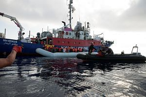 Migrants being rescued by the crew of German NGO Mission Lifeline in the Mediterranean Sea on Thursday. Italy's new government is digging its heels in on campaign promises to stop the influx of migrants, threatening to seize rescue ships or barring t