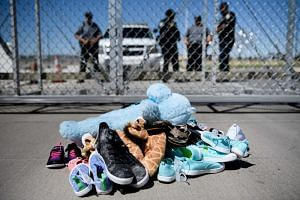 Security personal stand before shoes and toys left at the Tornillo Port of Entry in Texas, where minors crossing the border without proper papers have been housed after being separated from adults, on June 21, 2018.