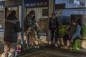 Homeless men sit and chat outside a pawn shop in Henderson, a suburb of Auckland, New Zealand, on June 5, 2018.