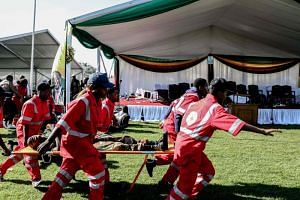 Injured people are evacuated after an explosion at the stadium in Bulawayo where Zimbabwe President just addressed a rally on June 23, 2018.