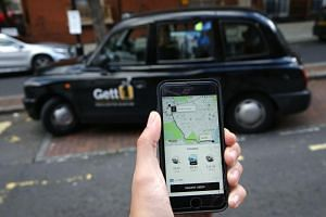 A person with a smartphone showing the App for ride-sharing cab service Uber in London on Sept 22, 2018.