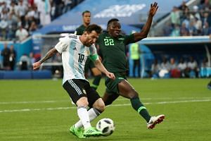 Lionel Messi (left) scoring a goal during the Russia 2018 World Cup Group D football match between Nigeria and Argentina at the Saint Petersburg Stadium in Saint Petersburg, on June 26, 2018.