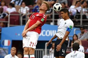 Denmark's forward Andreas Cornelius (left) vies with France's defender Raphael Varane during the Russia 2018 World Cup Group C football match between Denmark and France at the Luzhniki Stadium in Moscow on June 26, 2018.