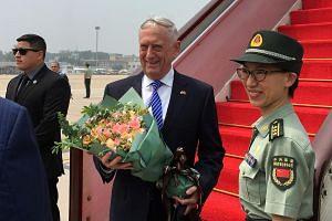 US Defense Secretary Jim Mattis receiving a bouquet upon arrival at an airport in Beijing.