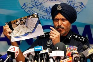Malaysia's Commercial Crime Investigation Department chief Amar Singh Ishar Singh showing a photo of some of the items seized, at a Kuala Lumpur news conference yesterday.