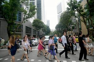 File photo showing pedestrians on the road in Singapore's central business district during the lunch hour, on June 29, 2018.