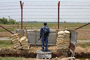 A Myanmar border guard keeps watch near the Taung Pyo Letwe reception camp overlooking the border with Bangladesh in Rakhine state on May 1, 2018.