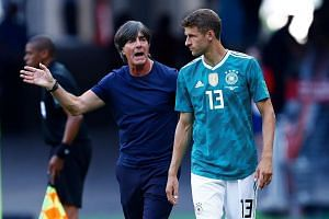 German coach Joachim Low speaks with forward Thomas Muller ahead of a substitution during the World Cup match against South Korea.