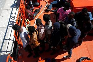 Migrants intercepted aboard dinghies off the coast in the Strait of Gibraltar, stand on a rescue boat after arriving at the port of Barbate, southern Spain, on June 27, 2018.