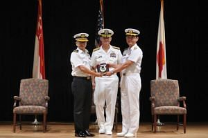 Rear-Admiral Saw Shi Tat (left) taking over the command of Combined Task Force 151 from outgoing Commander RADM Daisuke Kajimoto at the Naval Support Activity in Bahrain on June 28, 2018.