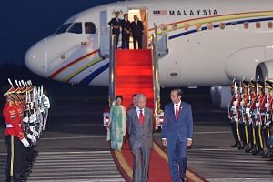 Indonesian President Joko Widodo (right) welcoming Malaysian Prime Minister Mahathir Mohamad at the Halim Perdanakusuma International Airport in Jakarta yesterday. This is Dr Mahathir's first visit to a South-east Asian nation after becoming premier
