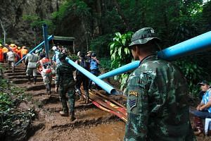 Thai military personnel carrying pipes to drain water from inside the flooded cave in northern Chiang Rai province, during the rescue operation yesterday. The underwater search had to be halted as water levels rose amid the relentless rainfall.