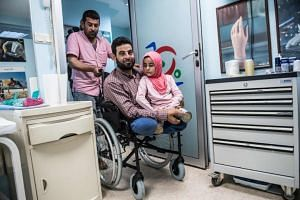 Eight-year-old Syrian girl Maya and her father, both born without legs, arrive to an Istanbul clinic on June 29, 2018, to get prosthetic legs after being evacuated from Syria.