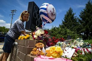 Christine Feldmann lays down flowers at the makeshift memorial outside the Capital Gazette newsroom in Annapolis, on June 29, 2018.