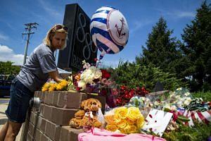 Christine Feldmann lays down flowers at the makeshift memorial outside the Capital Gazette newsroom in Annapolis, on June 29, 2018.