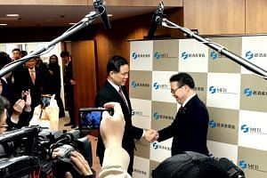 Singapore's Minister for Trade and Industry Chan Chun Sing and Japan's Minister of Economy, Trade and Industry Hiroshige Seko shake hands before a bilateral meeting in Tokyo on June 30, 2018.