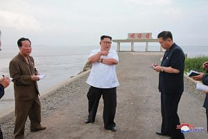 North Korean leader Kim Jong Un (centre) speaking to officials at Sindo County, North Phyongan Province, North Korea. NBC quoted five US officials as saying that in recent months North Korea had stepped up production of enriched uranium for nuclear w