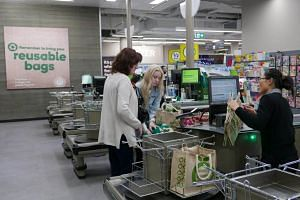 Shoppers checkout at a plastic bag-free Woolworths supermarket in Sydney, on June 15, 2018.