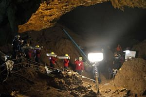Thai officials carry oxygen tanks through a cave complex during a rescue operation for a missing football team at the Tham Luang cave in Tham Luang Khun Nam Nang Noon Forest Park in Chiang Rai province, on June 30, 2018.