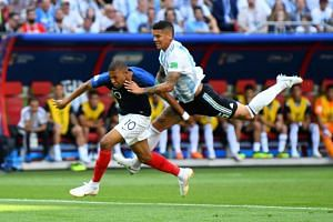Argentina's Marcos Rojo fouls France's Kylian Mbappe in the penalty area.