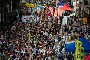 People attending a protest march meant to coincide with the 21st anniversary of the handover, on July 1, 2018.