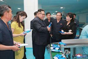 Kim Jong Un (centre) and his wife Ri Sol Ju (in yellow) visiting the Sinuiju Cosmetics Factory in Sinuiju.