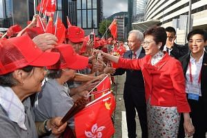 Hong Kong Chief Executive Carrie Lam greeting members of the public before the flag-raising ceremony for the anniversary of the establishment of the Hong Kong Special Administrative Region at Golden Bauhinia Square in Wan Chai yesterday. City residen