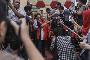 Newly elected Umno president Ahmad Zahid Hamidi arriving at a press conference in Kuala Lumpur yesterday, with his deputy Mohamad Hasan (behind him). Mr Zahid vowed to give his two main challengers key roles, but Mr Khairy said in a tweet he had reje