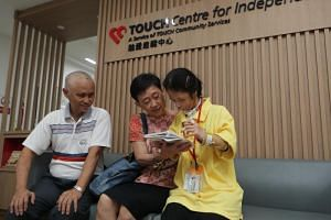 Ms Kwan Shi En with her parents at Touch Community Services' new day activity centre in Bukit Merah Central.