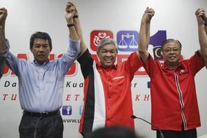 New Umno president Ahmad Zahid Hamidi (centre) and his deputy Mohamad Hasan (left) celebrate their winning during a press conference in Kuala Lumpur on July 1, 2018.