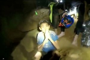 The trapped boys greeting members of the Thai rescue team in this still image taken from a Facebook video by the Thai Navy Seals, posted July 3, 2018.