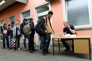 A German police officer registering refugees who travelled through Hungary and Austria, at a train station in Freilassing on Sept 15, 2015.