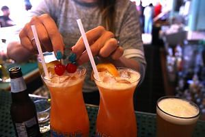 A bartender at Wipeout Bar & Grill makes cocktails that have paper straws in San Francisco, California.