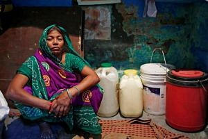 Sushila Devi, whose husband and son died after a brawl with neighbours over water in March, sits next to water containers inside her house in New Delhi, India,  on June 27, 2018.