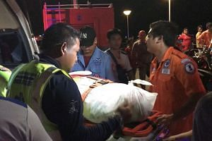 Thai rescue personnel carry a body bag containing the recovered body of passenger of the capsized tourist boat.