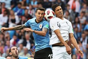Matias Vecino (left) of Uruguay in action against Raphael Varane of France.