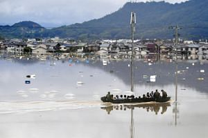 Residents are rescued from a flooded area by Japan Self-Defense Force soldiers in Kurashiki, southern Japan, on July 7, 2018.