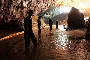 Thai navy divers inside the cave, in a photo released by the Royal Thai Navy. Rescuers have established a line to pump in fresh air and have withdrawn nonessential workers to preserve oxygen levels. Rescuers in the flooded cave in a photo released by