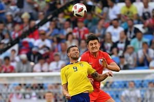 Sweden's forward Marcus Berg (left) heads the ball with England's defender Harry Maguire.