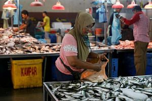 People buy fish at a wet market in Johor Bahru, Malaysia. According to a UN report, fish consumption reached an all-time high of 20.2kg per person from 9kg in 1961.