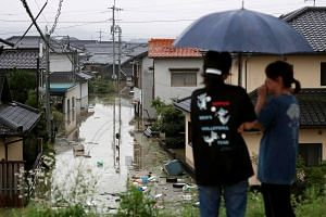 Residents look over the flooded town by heavy rain in Kurashiki, Okayama Prefecture, western Japan, on July 7, 2018.
