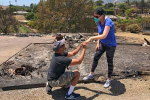 Ishu and Laura Rao return to the rubble of their home, which they lost in a wildfire, to retrieve their wedding ring, in Alameda, California, US, on July 8, 2018.