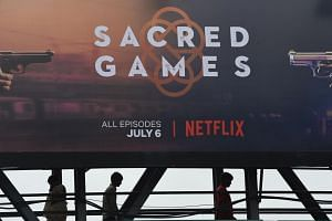 Indian commuters walk below a poster of Sacred Games, the upcoming Indian series on Netflix, in Mumbai.