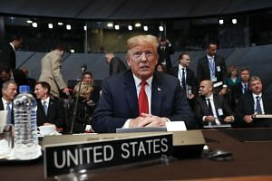 US President Donald Trump takes his seat as he attends the multilateral meeting of the Nato in Brussels, Belgium, on July 11, 2018.