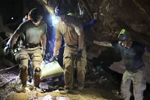 Rescue personnel carrying a member of the Wild Boars Thai youth football team on a stretcher during the rescue operation inside the Tham Luang cave in Khun Nam Nang Non Forest Park in Mae Sai district, on July 11, 2018.