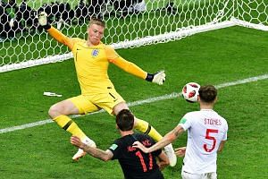 Croatia's forward Mario Mandzukic (centre) scores his team's second goal past England's goalkeeper Jordan Pickford (left) during the 2018 World Cup semi-final football match between Croatia and England at the Luzhniki Stadium in Moscow, on July 11, 2