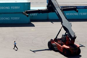 File photo of a worker running near a crane at a container port in Incheon, west of Seoul.