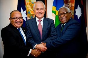 Australian Prime Minister Malcolm Turnbull poses with Papua New Guinea Prime Minister Peter O'Neill and Solomon Islands Prime Minister Rick Houenipwela at the Brisbane Commonwealth Parliamentary Office on July 11, 2018.