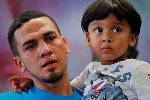 Javier, a 30 year old from Honduras, holds his four-year-old son, William, after they were separated for 55 days.