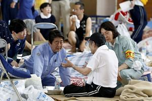 Japanese Prime Minister Shinzo Abe visiting evacuated residents at a makeshift evacuation center in the flood-devastated town of Kurashiki in Okayama Prefecture, western Japan, on July 11, 2018.